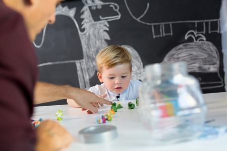 Cute little playfull toddler boy at child therapy session. Private one on one homeschooling with didactic aids. Stock Photo - 87592401