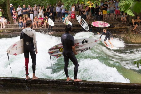 Munich, Germany, June 24, 2015: Surfers practicing their skill on an artificial wave situated on Isar river channel in Englischer garten, Munich central park, on 24th of June, 2015 in Munich, Germany. Stok Fotoğraf - 87543898