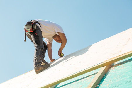 Carpenter roofer at work with wooden roof construction. Stockfoto