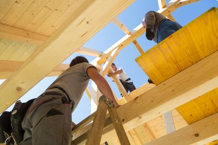 Constructores de techos que montan construcciones de techos de madera prefabricados. Concepto de la industria de la construcción. Foto de archivo