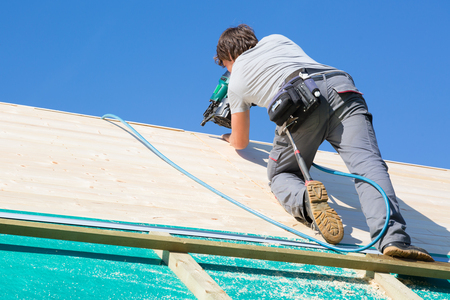 Carpenter roofer at work with wooden roof construction. Stock Photo
