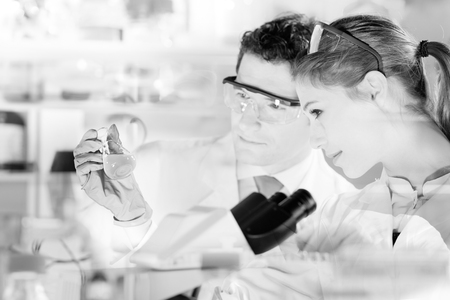 doctoral: Chemical laboratory. Attractive young PhD student and her post doctoral supervisor scientist observing the blue indicator color shift after the solution destillation. black and white image.