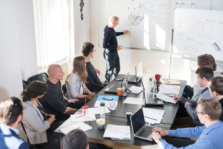 Relaxed informal IT business startup company meeting. Team leader discussing and brainstorming new approaches and ideas with colleagues. Startup business and entrepreneurship concept. Stock Photo