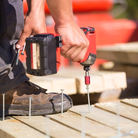 Laborer working with cordless battery electric screwdriver on construction site. Foto de archivo