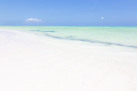 Solitary kite surfer kite surfing on picture perfect white sandy beach with turquoise blue sea, Paje, Zanzibar, Tanzania. Copy space. Horizontal composition.