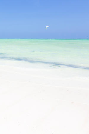 Solitary kite surfer kite surfing on picture perfect white sandy beach with turquoise blue sea, Paje, Zanzibar, Tanzania. Copy space. Vertical composition. Imagens