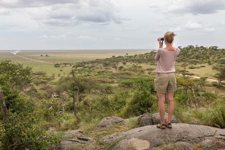 女性観光客は、セレンゲティ国立公園、タンザニア、アフリカのアフリカのサファリに双眼鏡でみる。