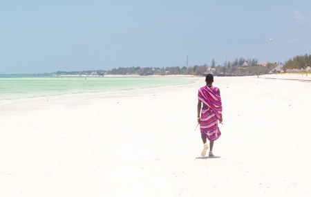 Unrecognizable Maasai warrior walking on picture perfect tropical sandy beach of Paje, on Zanzibar island, Tanzania, East Africa.