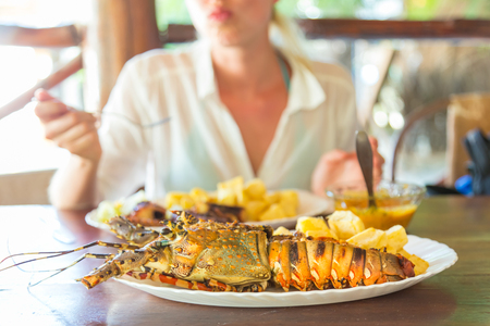 Lady on tropical vacations eating grilled lobster served with potatoes and coconut sauce. Reklamní fotografie - 89723791