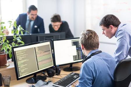 Entreprises en démarrage et résolution de problèmes d?entreprenariat. Les jeunes programmeurs d'intelligence artificielle et les développeurs de logiciels informatiques font du brainstorming et de la programmation sur un ordinateur de bureau dans une entreprise en démarrage se partagent l'espace de travail.