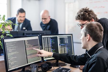 Rozwiązywanie problemów związanych ze start-upami i przedsiębiorczością. Młodzi programiści sztucznej inteligencji i programiści IT wspólnie prowadzą burzę mózgów i programują na komputerze stacjonarnym w nowo powstałej firmie.