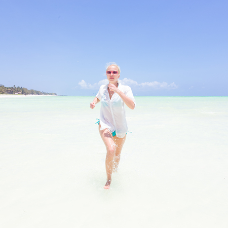 Young slim fit woman wearing white beach tunic running in sea water making water splashes with her legs. Vacation concept. Summer mood. Tropical beach setting. Paje, Zanzibar, Tanzania. Stock Photo