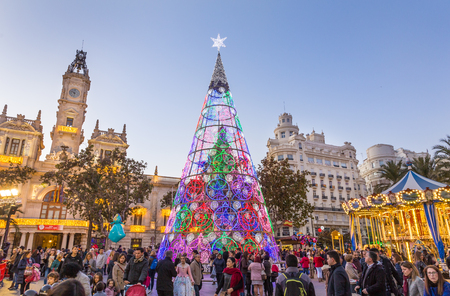 Valencia, Spain - Dec 16, 2017: People having fun on Christmas fair with colorful christmas tree and carousel on Modernisme plaza of the city hall on 16th of December, 2017 in Valencia, Spain.