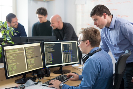 Startup business and entrepreneurship. Young software developers team brainstorming and programming on desktop computer in startup company share office space. Stockfoto