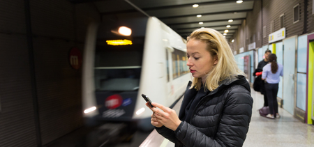 Young casual woman using mobile phone in her hand waiting on the platform of a metro station for metro to arrive. Public transport.
