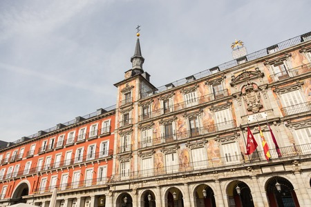 Detail of a decorated facade with traditional windows and balconies at the Palza Mayor, Madrid, Spain.