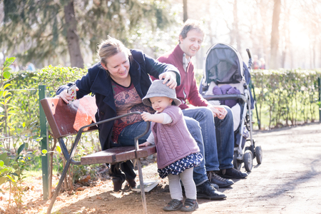 Young happy family with cheerful child having fun in park on sunny day. Standard-Bild