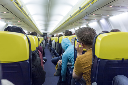 Interior of low priced commercial airplane with passengers on seats.