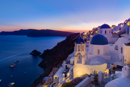Cityscape of Oia, traditional greek village with blue domes of churches, Santorini island, Greece at dusk.