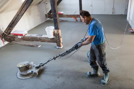 Arbeider die zand en cementdekvloer uitvoert en polijst. Zand- en cementvloeren.