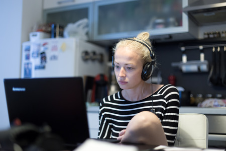 Woman in her casual home clothing working and studying remotely from her small flat late at night. Home kitchen in background. Great flexibility of web-based courses and study programmes. Standard-Bild