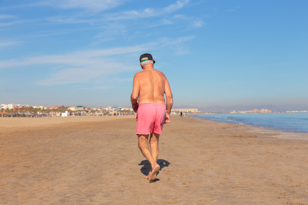 Rear view of unrecognizable shirtless senior man walking on empty sandy beach of Valencia, Spain in winter. Standard-Bild