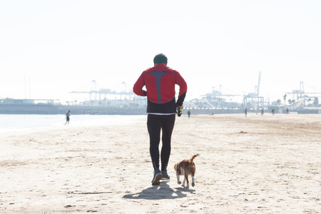 Senior Man Exercising On Empty Sandy Beach With His Dog Running Next To Him. Valencia, Spain in wintertime.