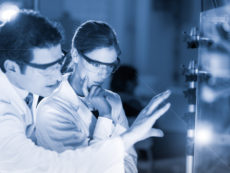 Portrait of a focused electrical engineering researchers in their working environment checking the phenomenon of breaking laser beam on the glass surface. Greyscale blue toned image.