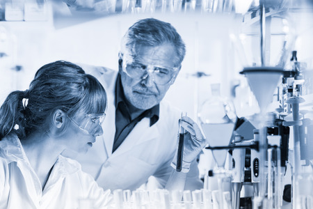Health care researchers working in life science laboratory. Young female research scientist and senior male supervisor observing indicator color shift in tube. Greyscale blue toned image.