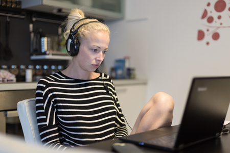 Woman in her casual home clothing working and studying remotely from her small flat late at night. Home kitchen in background. Great flexibility of web-based courses and study programmes. Banque d'images