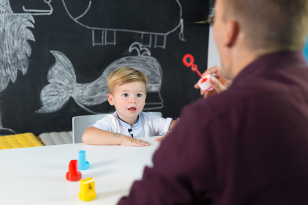Cute little playfull toddler boy at speech therapy session. Private one on one homeschooling with didactic aids. Stock Photo