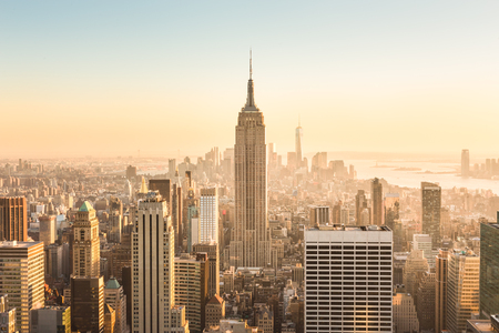 New York City. Manhattan downtown skyline with illuminated Empire State Building and skyscrapers at amazing golden sunset. USA. Stock Photo