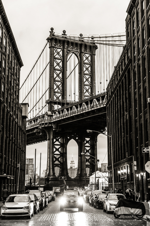 Manhattan Bridgeas seen from Washington street in Brooklyn, New York City, USA. Motion blured jogger running in foreground. Black and white image. Stock Photo