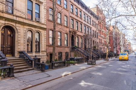 Szenischer Baum zeichnete Straße von historischen Brownstone-Gebäuden in der Westdorfnachbarschaft von Manhattan in New York City, NYC USA. Traditionelles gelbes Taxiauto, das entlang Straße fährt.