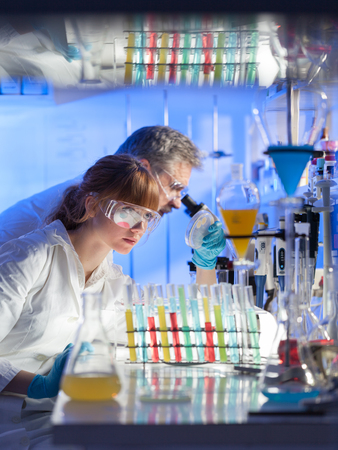 Scientists researching in scientific laboratory. Young female scientist and her senior male supervisor looking at the cell colony grown in the petri dish in the life science research laboratory. Stock Photo