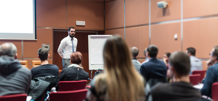 Public Speaker Giving a Talk at Business Meeting. Audience in the conference hall. Skilled coach answers questions of participants of business training. Business and Entrepreneurship concept. Stok Fotoğraf