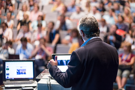 Speaker giving a talk on corporate business conference. Unrecognizable people in audience at conference hall. Business and Entrepreneurship event. Stock Photo