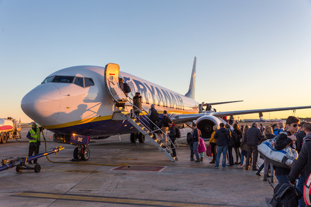 Valencia, Spain - Dec 17, 2017: Passangers boarding on Ryanair commercial low-cost flight on Valencia airport at sunset on 17th of December, 2017 in Valencia.