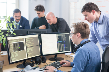 Startup business and entrepreneurship problem solving. Young AI programmers and IT software developers team brainstorming and programming on desktop computer in startup company share office space. Stockfoto