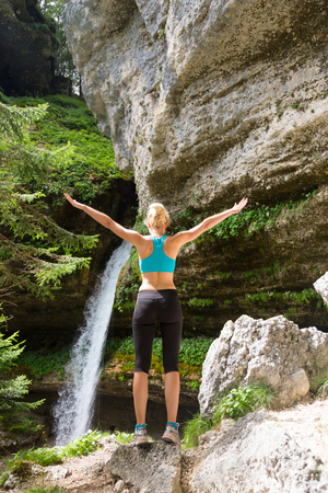 Active woman raising arms inhaling fresh air, feeling relaxed and free in beautiful natural environment under Pericnik waterfall in Vrata Valley in Triglav National Park in Julian Alps, Slovenia. Stock Photo