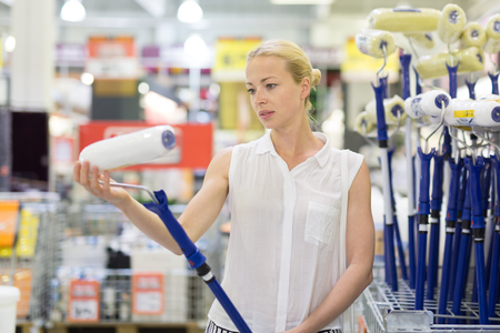 Young independent woman buying paint roller and tools for house decoration in hardware store.