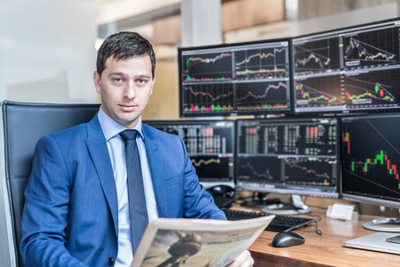 Business portrait of confident stocks broker holding a business newspaper in traiding office with multiple computer screens full of index charts and data analyses.