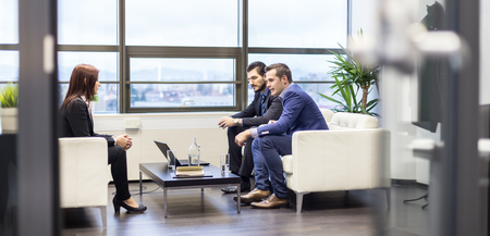 Businessmen interviewing female candidate for job in modern corporate office. Woman during job interview and two elegant members of management. Through glass candid view.
