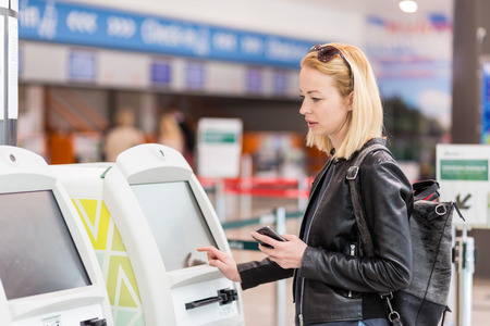 Casual caucasian woman using smart phone application and check-in machine at the airport getting the boarding pass. Modern technology on airport. Banque d'images
