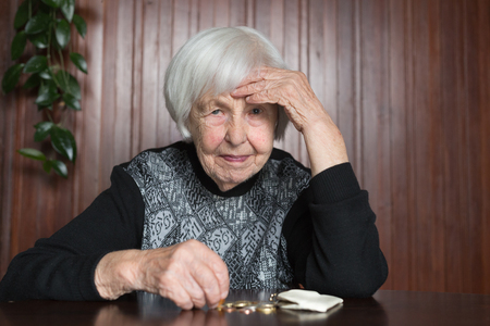 Elderly 95 years old woman sitting miserably at the table at home and counting remaining coins from the pension in her wallet after paying the bills. Foto de archivo