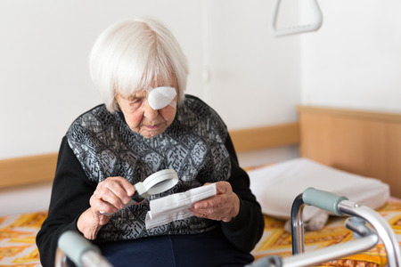 Visually impaired elderly 95 years old woman sitting at the bad trying to read her medical therapy prescription with magnifying glass due to eyesight problems.