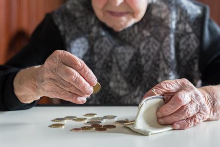 Ältere 95-jährige Frau, die zu Hause kläglich am Tisch sitzt und nach Bezahlung der Rechnungen die restlichen Münzen aus der Rente in ihrer Brieftasche zählt. Standard-Bild