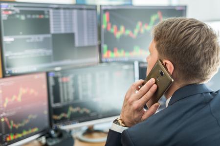 Widok przez ramię i makler giełdowy prowadzący transakcje online podczas przyjmowania zleceń przez telefon. Wiele ekranów komputerowych z wykresami i analizami danych w tle.