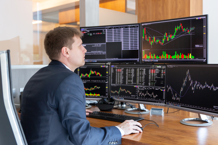Businessman trading stocks. Stock traders looking at graphs, indexes, numbers and analyses on multiple computer screens in modern trading office. Imagens