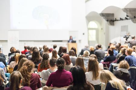 Orateur féminin donnant une présentation en salle de conférence à l'atelier universitaire Public dans la salle de conférence. Vue arrière d'un participant non reconnu dans l'auditoire. Événement de conférence scientifique. Banque d'images